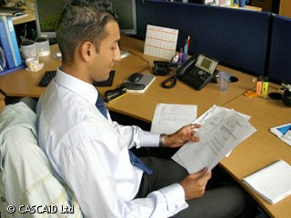 A man is sitting at an office desk, reading a paper document.