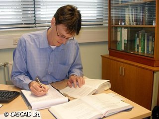 A man is sitting at a desk.  He is looking at two open books, and writing onto a notepad.