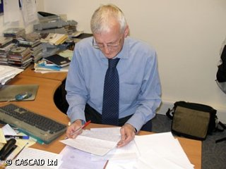 A man is sitting at a desk in an office.  He is looking at various paper documents in front of him.  There is a computer on the desk.