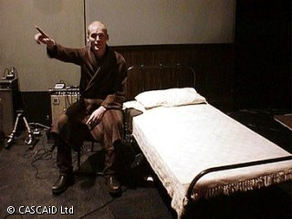 A man, wearing a dressing gown, is sitting on a chair, next to a bed.  He is pointing at something.