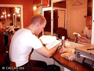 A man is sitting in front of a large mirror.  He is reading a sheet of paper.