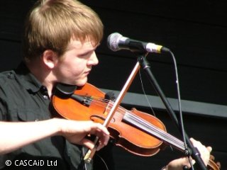 A man is standing behind a microphone, playing a fiddle.
