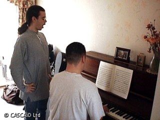 A man is sitting, playing a piano.  There is a man standing next to him, singing.