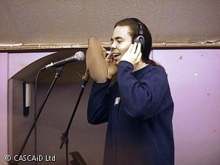 A man is singing into a microphone.  He is wearing headphones.