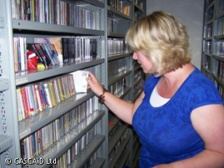 A woman is standing in between two rows of shelves, full of CDs.  She is removing a CD.