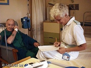 A man is sitting in a chair next to a hospital bed.  A woman, wearing a white uniform, is sitting on the bed.  She is making notes.