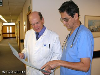 A man, wearing a white lab coat, is talking to a man wearing a blue hospital doctor's uniform.  They are both looking at a sheet of paper.