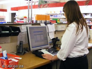 A female pharmacist is holding a green prescription slip and looking at a computer screen.
