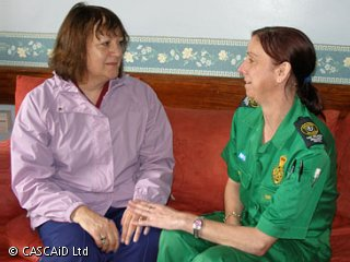 Two women, one wearing a paramedic's uniform, are sitting on a sofa.  They are talking.