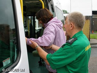 A man, wearing a paramedic's uniform, is helping a woman to climb into an ambulance.