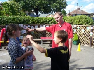 A man and three children of various ages are standing outdoors.  The man is explaining a game.  The eldest child, a girl, is holding a football.
