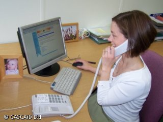 A woman is sitting at a desk, using a computer.  She is speaking on a telephone.