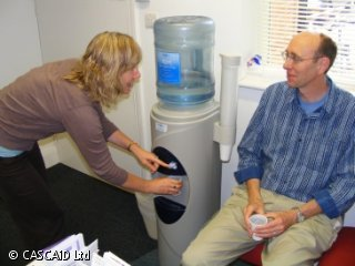 A man is sitting on a chair, next to a water cooler.  A woman is standing next to him, pouring a glass of water. They are talking.