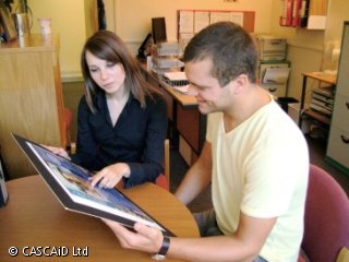 A woman and a man are sitting at a table, talking.  They are looking at a poster on a small display board.