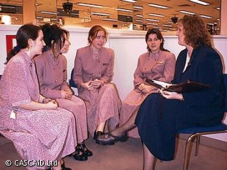 Four women, wearing shop uniforms, are sitting, talking to another woman, who is wearing an office suit.
