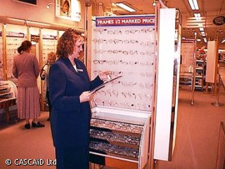 A woman is standing in a shop, next to a display of spectacles.  She is holding a clipboard.