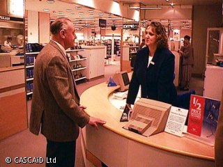 A woman is standing behind a shop counter.  She is talking to a man, who is standing in front of the counter.