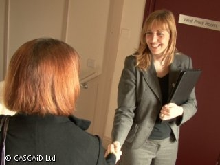 Two women are shaking hands with each other.  One of them is holding a black folder; she is smiling at the other woman.