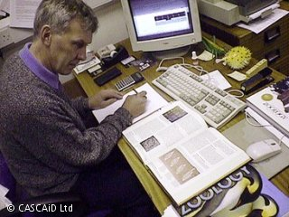 A man is sitting at a desk, looking at a book and making notes on a notepad.