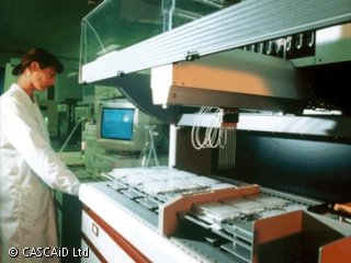 A woman, wearing a white lab coat, is standing in a laboratory, next to a large piece of machinery.
