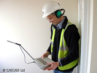 A man, wearing a green tabard and headphones, is standing in a room.  He is holding a piece of monitoring equipment.