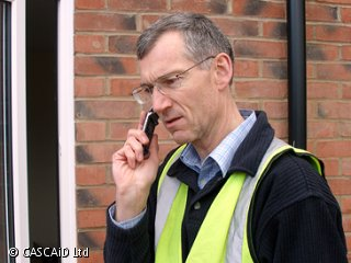 A man, wearing a green tabard, is standing outside.  He is speaking on a telephone.