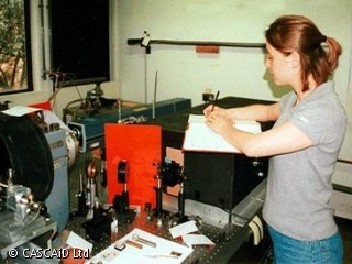 A woman is standing next to a large piece of scientific equipment.  She is writing into a book.