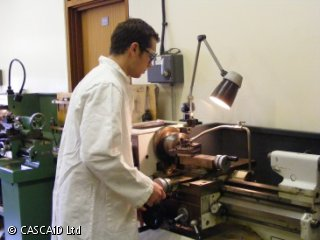 A man, wearing a white lab coat and safety glasses, is operating a lathe.