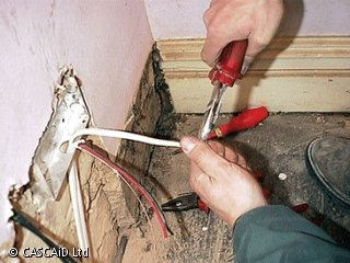 A man, wearing a boiler suit, is crouching down in the corner of a room.  He is cutting some wires that are attached to a wall.