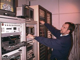 A man is standing in a recording studio.  He is adjusting some of the broadcasting equipment, which lines the wall in front of him.