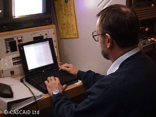 A man is sitting at a desk, using a laptop computer to set up equipment to record an outside broadcast.