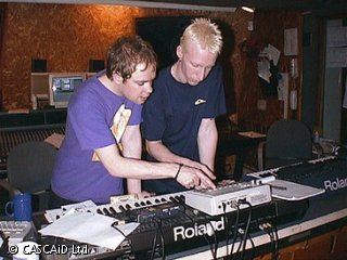 Two men are standing by an electronic keyboard, in a studio.  They are talking and pressing some buttons on a piece of sound recording equipment.