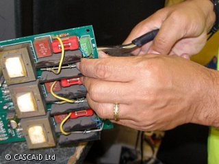 A man is using a pair of pliers to fix a circuit board, which is part of a TV set.