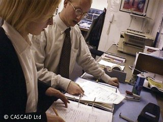A woman and a man are standing next to a table.  They are looking at the contents of an open folder.