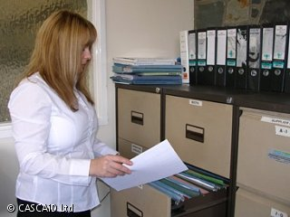 A woman is standing next to a filing cabinet.  One of the drawers is open and she has taken a sheet of paper from a file within the drawer.