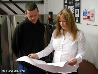 A woman and a man are standing, talking.  They are both looking at a large sheet of paper.