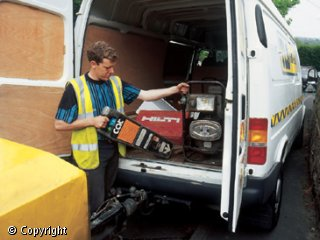 A man, wearing a yellow, reflective tabard, is removing tools and equipment from the back of a white van.