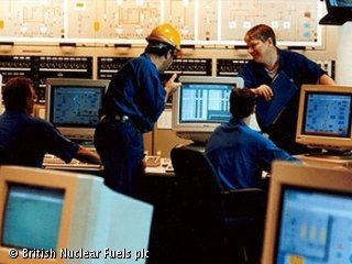 Four people are sitting at desks, in a large office.  They are using computers.  They are wearing blue uniforms, and one of them is wearing a hard hat.