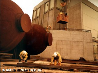 Two people, wearing hard hats and high visibility jackets, are crouching on the ground outside.  They are working on some long metal strips, on the ground of a nuclear plant.