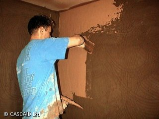 A man is standing in a room.  He is spreading plaster onto a wall.