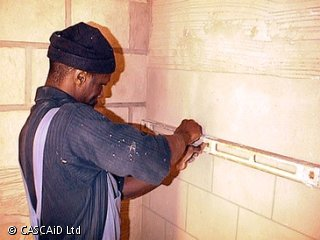 A man is standing next to a wall.  He is drawing a brick effect in the plaster.