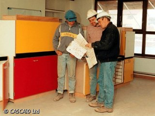 Three men, wearing hard hats, are standing in a room.  They are talking and looking at a large sheet of paper.