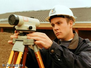 A man, wearing a hard hat, is standing in a field.  He is using a surveying device, which stands on a tripod.